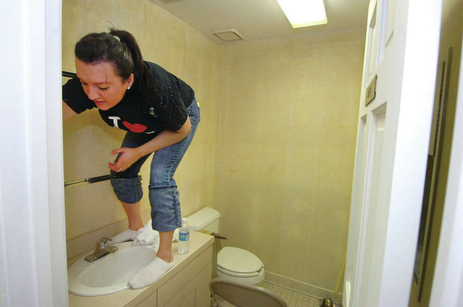 Hour Photo/ Alex von KleydorffAon employee Paula Restrepo sands the last of the wallpaper glue off the walls of a bathroom at the new offices of Ability Beyond Disability in Norwalk. / © 2012 Alex von Kleydorff/The Hour Newspapers