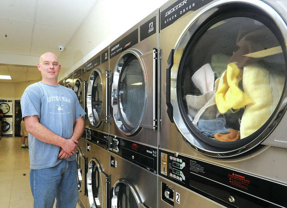 Hour photo/Matthew VinciThe Laundry Basket opened earlier this month at 15 Cross St. in the Goodwill Plaza. The facility is open 24 hours. The Laundry Basket offers Mac-Gray washers and dryers, as well as drop-off wash, dry and fold services. The facility also has free WiFi and three-screen televisions. Above, Bjorn Wisecup, co-owner of The Laundry Basket, at his Norwalk location on Cross Street.