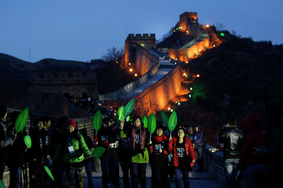 University students participate in a mini marathon in conjunction during the earth hour at the Great Wall of China in north of Beijing, China, Saturday, March 31, 2012. Hundreds of landmarks around the world including Washington's National Cathedral, London's Clock Tower, the Great Wall of China and Tokyo Tower will be dimmed at 8:30 p.m. local time, as part of a global effort to shine a spotlight on climate change. (AP Photo/ Vincent Thian) / AP