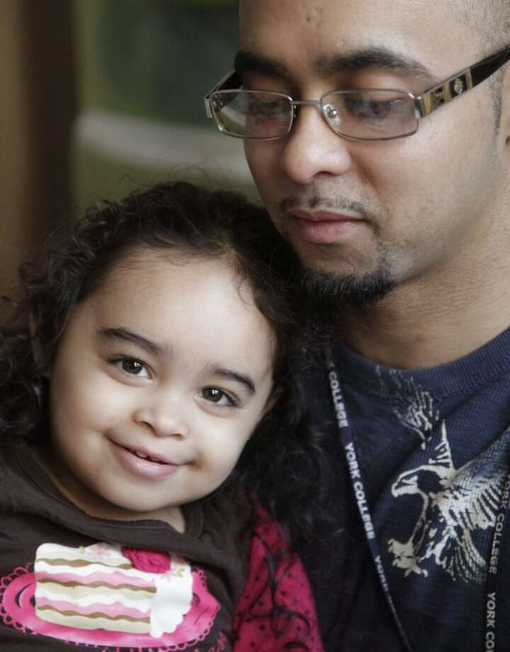 Cristina Astacio, 2, recently diagnosed with a mild form of autism, reacts as reads with her dad Christopher Astacio on Wednesday, March 28, 2012 in New York. Autism cases are on the rise again, largely due to wider screening and better diagnosis, federal health officials said Thursday, March 2012. (AP Photo/Bebeto Matthews)