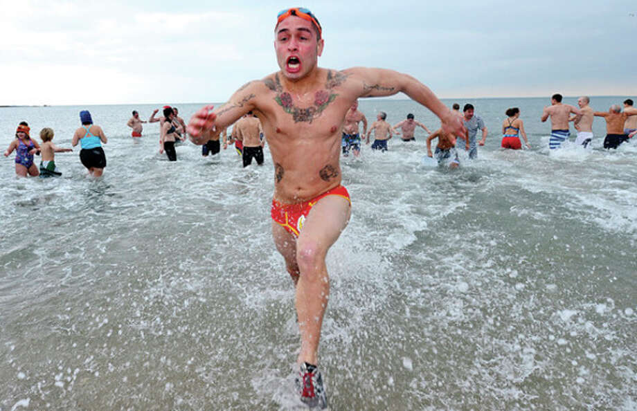 Hour photo / Erik TrautmannTeam Mossman Triathlon Club member Kenny Ildeefonso kicks off the New Year participating in the club's 10th annual 'polar plunge' at Compo Beach Tuesday morning that benefits Save the Children. / (C)2012, The Hour Newspapers, all rights reserved