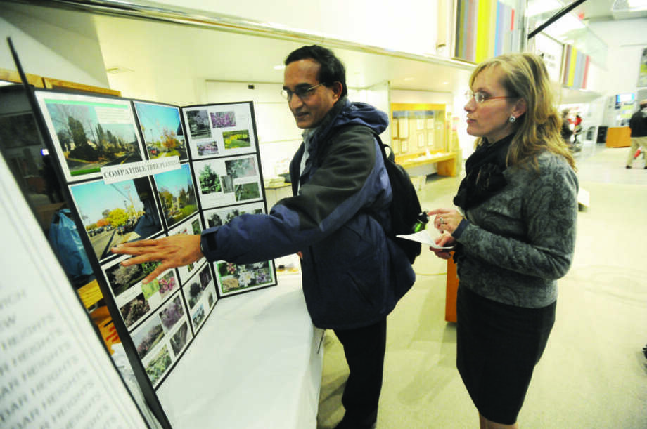 Katie Blint with CL&P communications speaks with Veera Karukonda about trees and utilities lines Tuesday. CL&P hosted an open house for residents at the Government Center in Stamford.