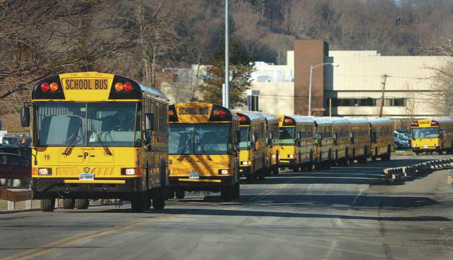 School buses travel down Kristine Lilly Way from Wilton High School to pick up students at Cider Mill on Thursday afternoon / 2013 The Hour Newspapers
