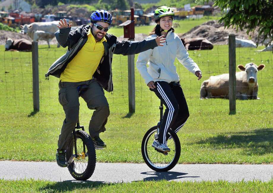 Scott Murawski, left, of Amsterdam and Liann Goldmann of Latham unicycle past cows at The Crossings Tuesday morning June 14, 2016 in Colonie, NY.  (John Carl D'Annibale / Times Union) Photo: John Carl D'Annibale