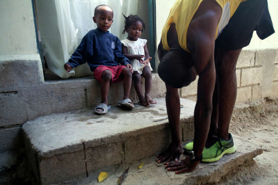 In this Jan. 8, 2013 photo, Astrel Clovis, a 42-year-old marathon runner, stretches his leg muscles outside his home as two of his young neighbors watch, in Petionville, a suburb of Port-au-Prince, Haiti. Like virtually all Haitians in the capital of 3 million, the runner's life was disrupted by the catastrophic earthquake on Jan. 12, 2010. Before the quake, he shared a three-bedroom house with his aunt and cousins, and dreamed of running his first marathon. The quake destroyed that house, along with about 100,000 homes across the capital and southern Haiti. The government put the death toll at 316,000, but no one knows how many people died. Clovis was lucky. He didn't lose any relatives, or close friends - or his marathon dreams. (AP Photo/Dieu Nalio Chery) / AP