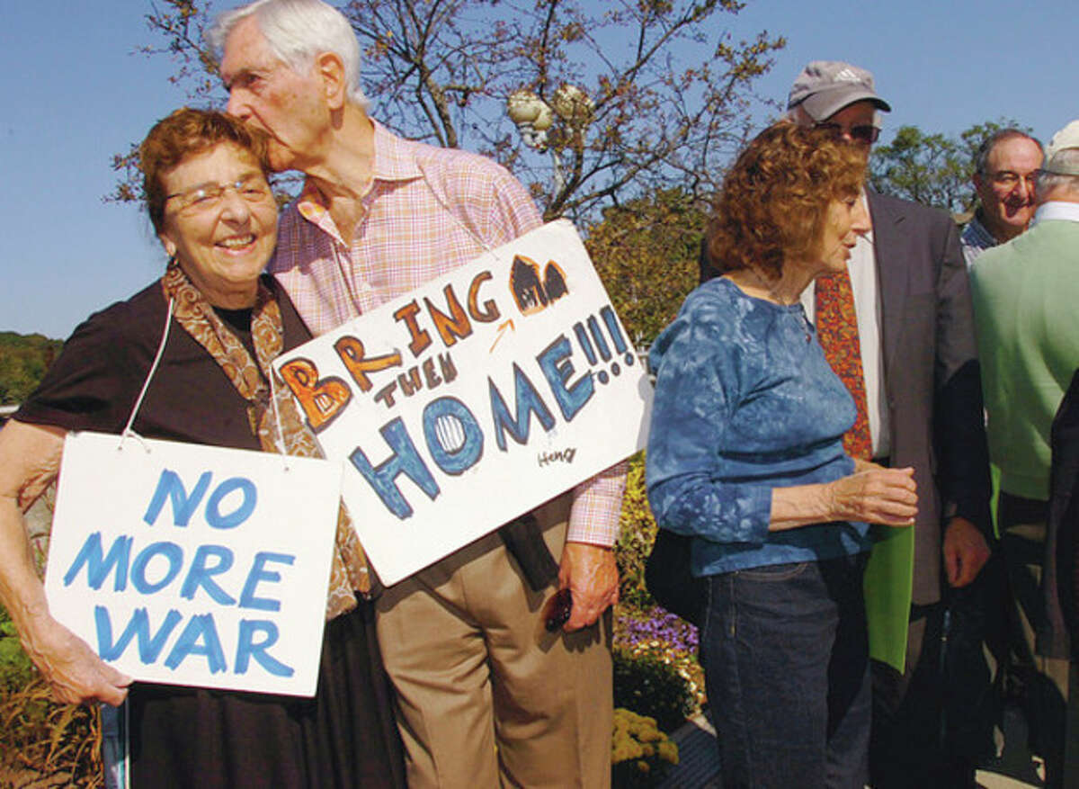 Sonny Fox gives a kiss to Estelle Margolis, wife of the late activist Manny Margolis, during the weekly protest against the war on the Ruth Steinkraus Bridge in Westport which Margolis started in 2001.