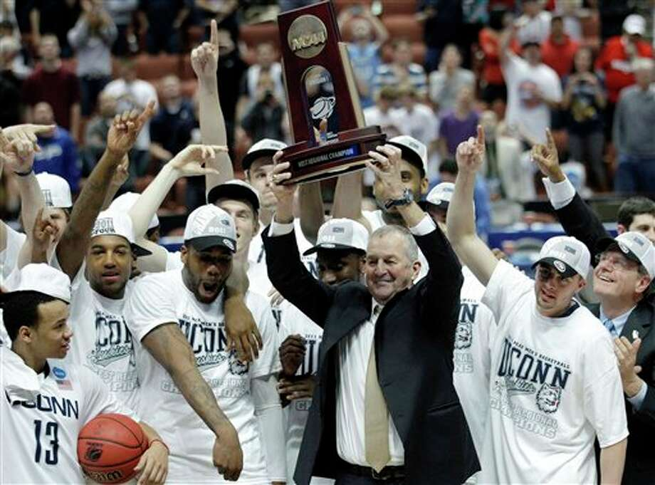 Connecticut head coach Jim Calhoun, holds the trophy and celebrates with his team after the NCAA West regional college basketball championship game, Saturday, March 26, 2011, in Anaheim, Calif. Connecticut beat Arizona 65-63. (AP Photo/Jae C. Hong) / AP