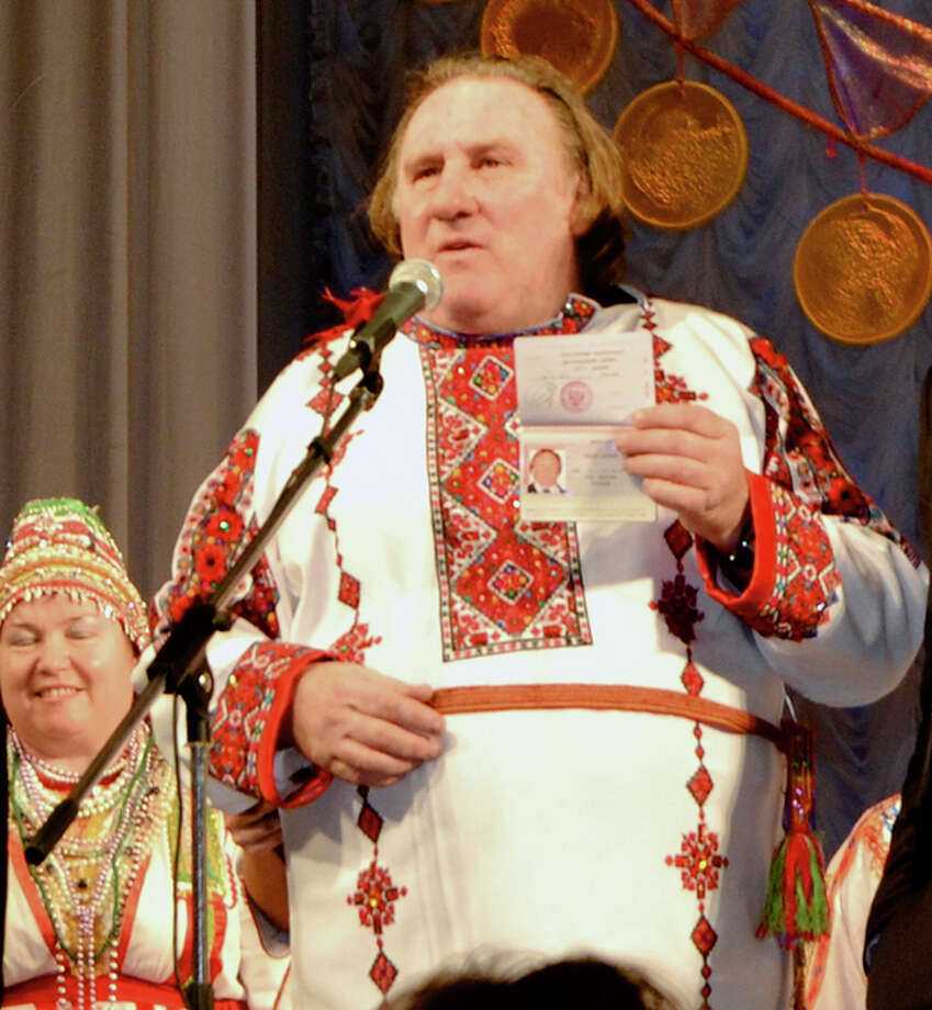 CORRECTING DATE TO SUNDAY JAN. 6 - French actor Gerard Depardieu poses with his new Russian passport on a theatre stage, wearing a traditional folk outfit, after he arrived in the city of Saransk, some 700 km (435 miles) east of Moscow, Russia, on Sunday, Jan. 6, 2013. Depardieu has received a Russian passport after flying to Russia for a late night dinner with Putin. Depardieu sought Russian citizenship as part of his battle against a proposed super tax on millionaires in France, and Putin granted his request last week. (AP Photo/Mordovmedia.ru) / Mordovmedia.ru