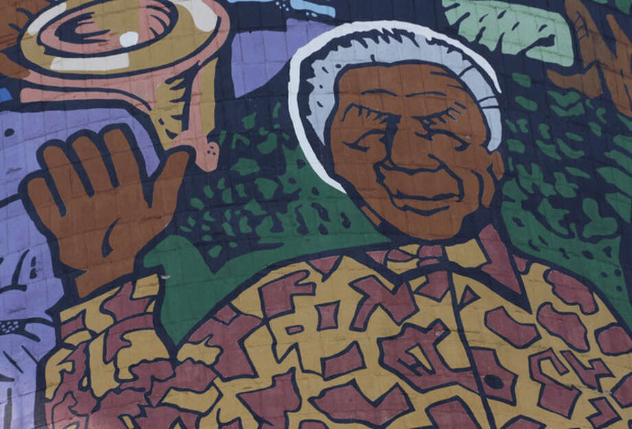 A giant portrait of former president Nelson Mandela adorns a cooling tower of a now defunct power station in Soweto, South Africa, Monday, Dec 31, 2012. Mandela is recovering at his Johannesburg home since being hopitalized for a lung infection and undergoing gallstone surgery. (AP Photo/Denis Farrell) / AP