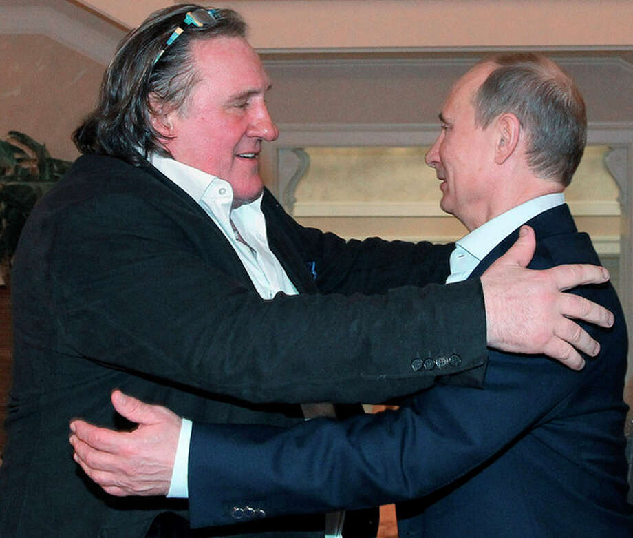 French actor Gerard Depardieu, left, greets Russian President Vladimir Putin after his arrival late Saturday, Jan. 5, 2013, at the president's residence in Sochi, the host city of the 2014 Winter Olympics. Depardieu has received a Russian passport after flying to Russia for a late night dinner with Putin. Depardieu sought Russian citizenship as part of his battle against a proposed super tax on millionaires in France, and Putin granted his request last week. (AP Photo/RIA-Novosti, Mikhail Klimentyev, Presidential Press Service) / ??? ???????