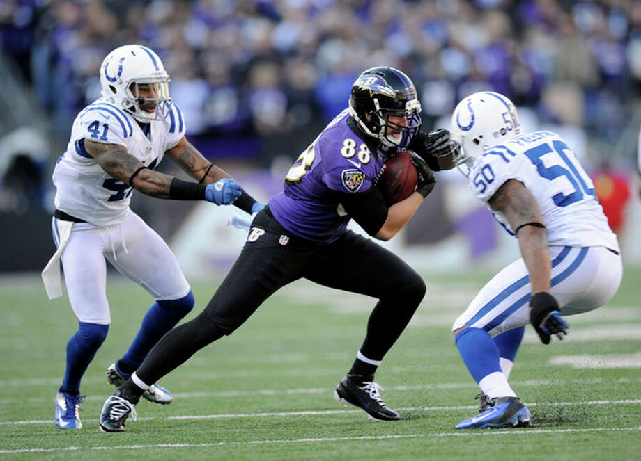Baltimore Ravens tight end Dennis Pitta (88) tries to get away from Indianapolis Colts free safety Antoine Bethea (41) and inside linebacker Jerrell Freeman (50) during the first half of an NFL wild card playoff football game Sunday, Jan. 6, 2013, in Baltimore. (AP Photo/Nick Wass) / FR67404 AP