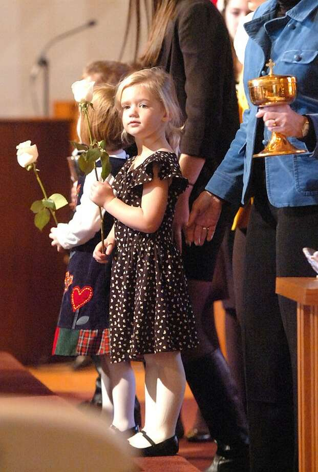 Hour Photo/Alex von Kleydorff. Family hold flowers during the Presentation of Gifts during the funeral for Chief Justice Robert J. Callahan at St. Jerome Church in Norwalk Monday