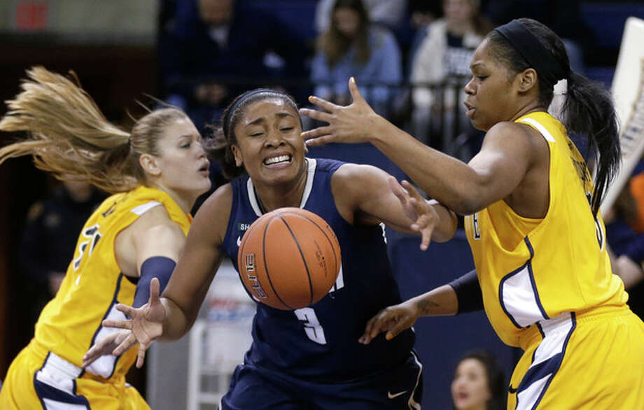Connecticut's Morgan Tuck (3) loses control of the ball as Marquette's Cristina Bigica, left, and Katie Young, right, defend in the second half of an NCAA college basketball game Saturday, Jan. 12, 2013, in Milwaukee. Connecticut won 85-51. (AP Photo/Jeffrey Phelps) / FR59249 AP