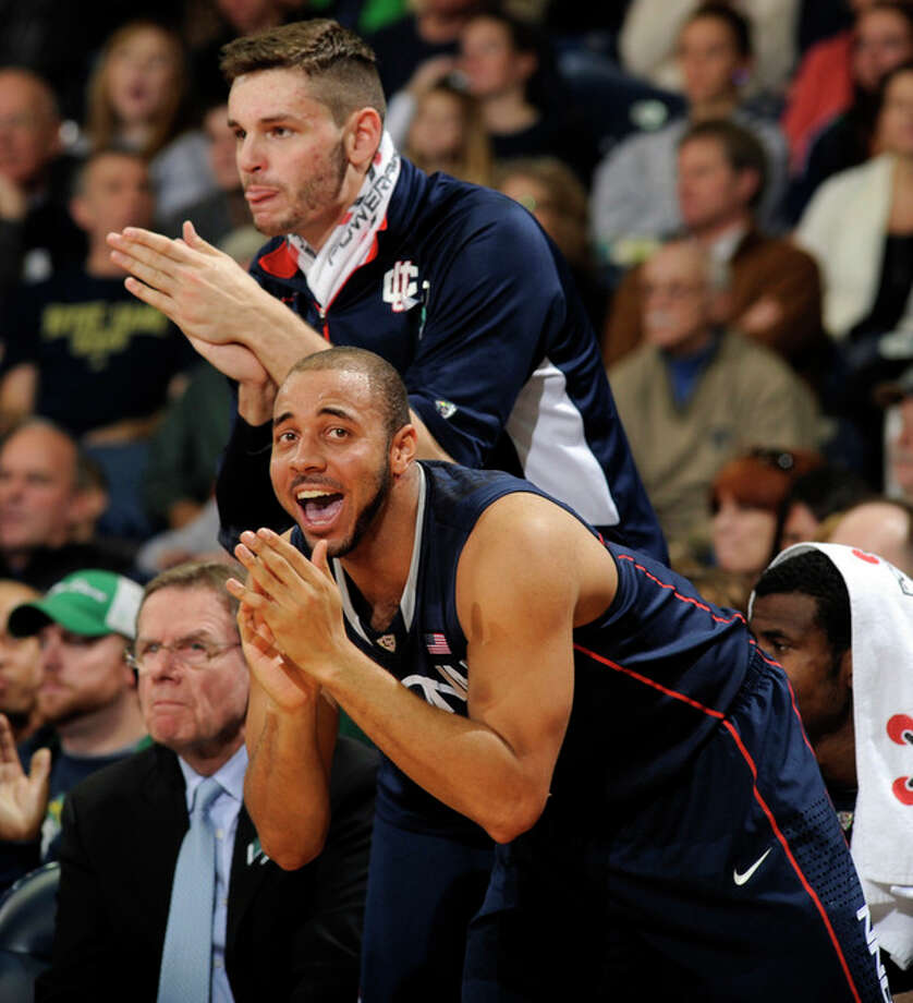 Connecticut's R.J. Evans foreground, and Enosch Wolf celebrate a play during the first half of an NCAA college basketball game against Notre Dame, Saturday, Jan. 12, 2013, in South Bend, Ind. In the foreground is R.J. Evans. (AP Photo/Joe Raymond) / FR25092 AP