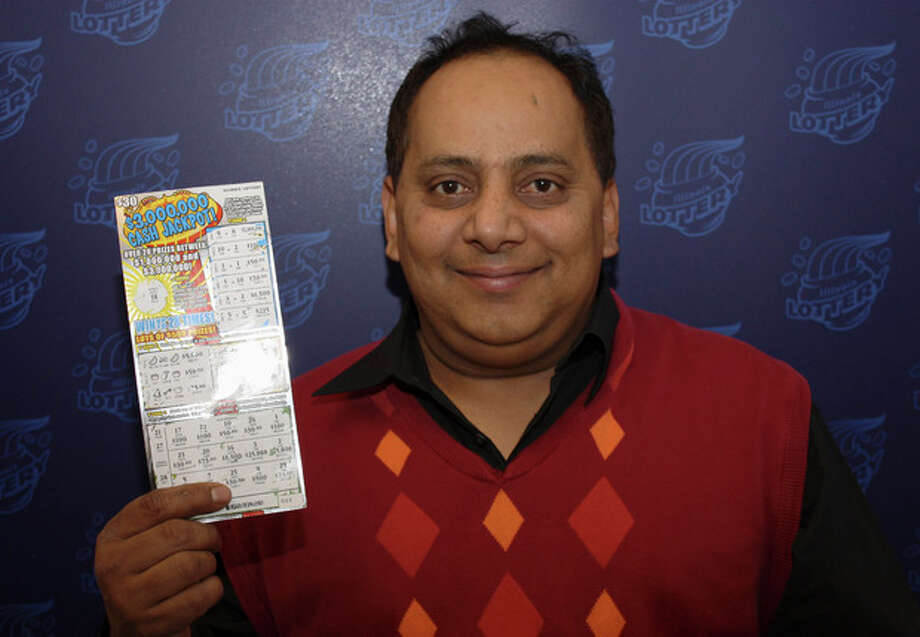 FILE - This undated file photo provided by the Illinois Lottery shows Urooj Khan, 46, of Chicago's West Rogers Park neighborhood, posing with a winning instant lottery ticket. On Friday, Jan 11, 2013, a Cook County judge granted authorities permission to exhume the body of the Chicago lottery winner who was fatally poisoned with cyanide just as he was about to collect his $425,000 payout. His July 20 death was initially ruled a result of natural causes. (AP Photo/Illinois Lottery, File) / Illinois Lottery