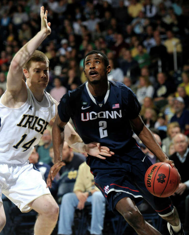 Connecticut forward DeAndre Daniels, right, drives the baseline as Notre Dame guard Scott Martin defends during the first half in an NCAA college basketball game, Saturday, Jan. 12, 2013, in South Bend, Ind. (AP Photo/Joe Raymond) / FR25092 AP