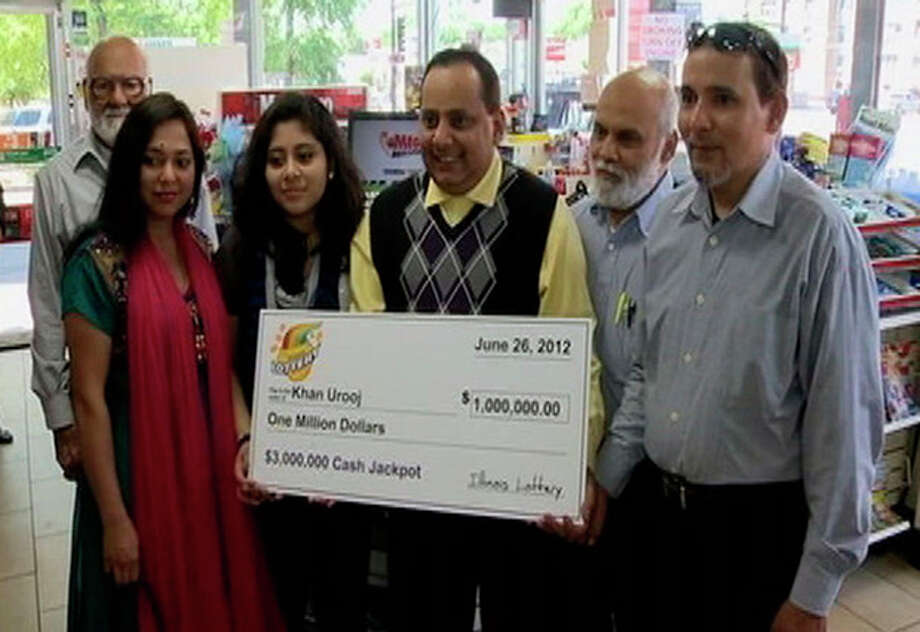 This June 2012 photo provided by WMAQ-TV in Chicago shows Urooj Khan, center, holding a ceremonial check in Chicago for $1 million as winner of an Illinois instant lottery game. At left, is Khan's wife, Shabana Ansari. Khan, 46, who owned several dry cleaning operations and some real estate, died suddenly on July 20, 2012, just days before he was to collect his winnings. Khan's death has been ruled a homicide. Court records show that Ansari has battled with his siblings over control of his estate, including his $425,000 prize money. A Cook County judge on Friday, Jan. 11, 2013, approved the exhumation of Khan's body. (AP Photo/Courtesy of WMAQ-TV in Chicago) / WMAQ-TV