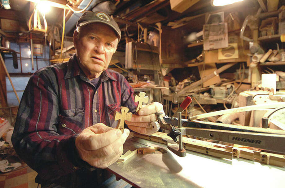 Hour photo / Alex von KleydorffGene Reilly shows some of the Celtic Crosses that he makes on his Scroll saw from hardwoods like Maple and Purple Heart in his woodshop. / 2013 The Hour Newspapers
