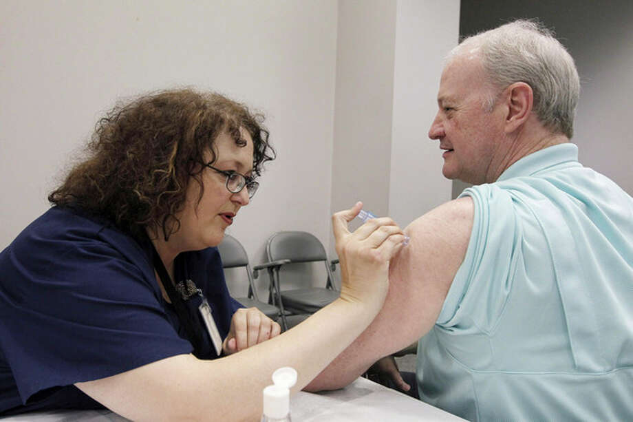 FILE - In this file photo taken Oct. 17, 2012, Bill Staples, a Mississippi Department of Health employee, is given a flu vaccine shot by registered nurse Rosemary Jones, also with the health department, in Jackson, Miss. A survey by Centers for Disease Control and Prevention researchers found that in 2011, more than 400 U.S. hospitals required flu vaccinations for their employees and 29 hospitals fired employees that were not vaccinated against the virus. (AP Photo/Rogelio V. Solis, File) / AP