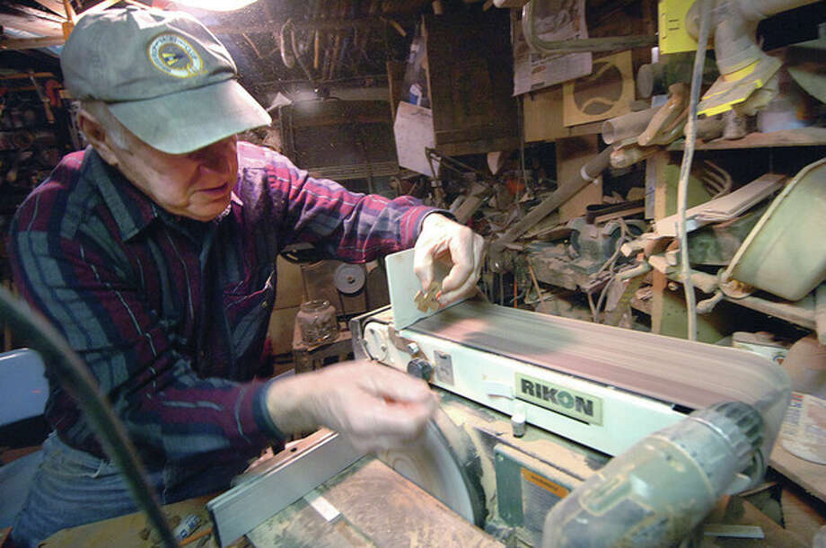 Clockwise, from left, Gene Reilly sands the corners of a Celtic Cross in his Norwalk woodworking studio; holds a hand-made excavator; and stands at Woods Pond, where the hockey goals are also his handiwork. / 2013 The Hour Newspapers