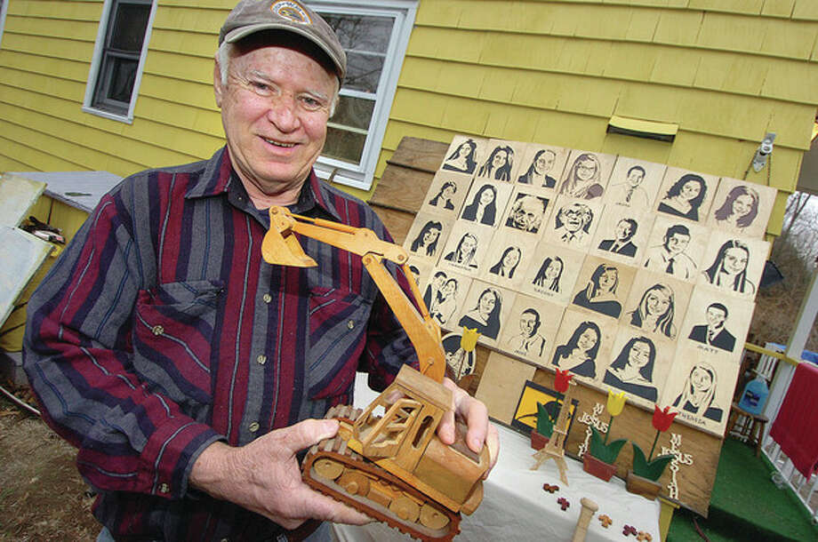 Hour Photo/Alex von Kleydorff. Gene Reilly holds a hand made excavator he made in his Norwalk Woodworking studio / 2013 The Hour Newspapers