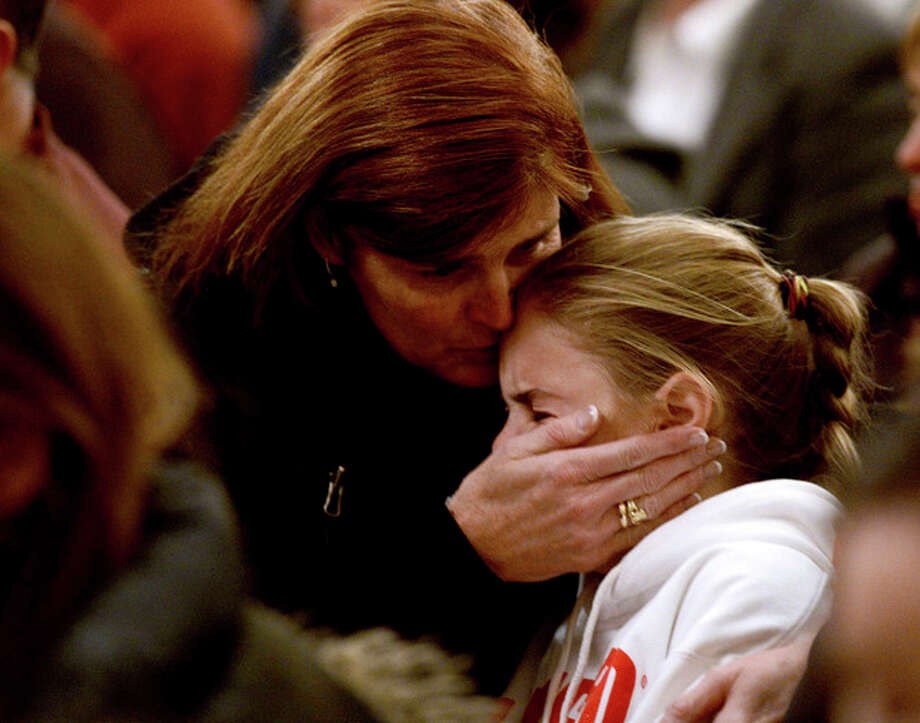A woman comforts a young girl during a vigil service for victims of the Sandy Hook Elementary shooting, Friday, Dec. 14, 2012, at St. Rose of Lima Roman Catholic Church in Newtown, Conn. (AP Photo/Andrew Gombert, Pool) / Pool EPA