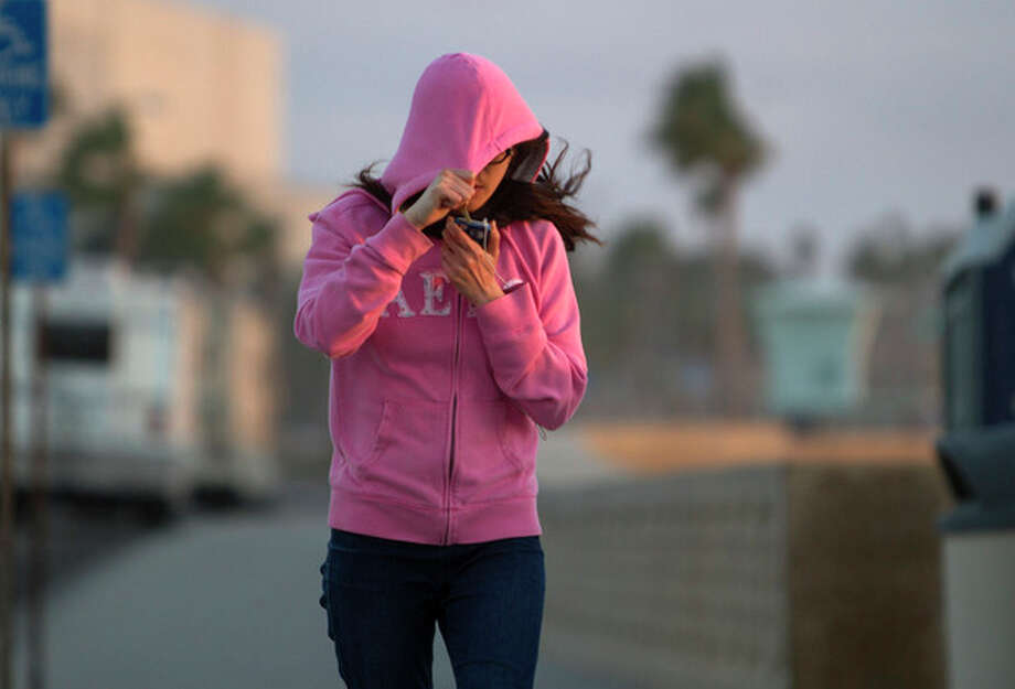 Fiona Chiang shields her face from blowing sand as she walks north on Carlsbad Boulevard in Carlsbad, Calif. Thursday, Jan. 10, 2013. Southern California is bracing for a cold snap that is expected to drop temperatures to a six-year low. (AP Photo/U-T San Diego, Bill Wechter) SAN DIEGO COUNTY OUT; NO SALES; COMMERCIAL INTERNET OUT; FOREIGN OUT / The U-T San Diego