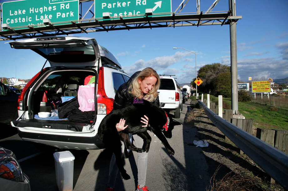 Heidi Blood carries her dog to the side of the road for a drink of water while waiting in line with her car along Interstate 5 north of Los Angeles on Friday, Jan. 11, 2013. The California Highway Patrol has partially reopened a 40-mile stretch of Interstate 5 north of Los Angeles that was closed for many hours due to snow. The CHP began escorting southbound motorists through the high mountain pass Friday morning. Northbound lanes are still closed. (AP Photo/Nick Ut) / AP