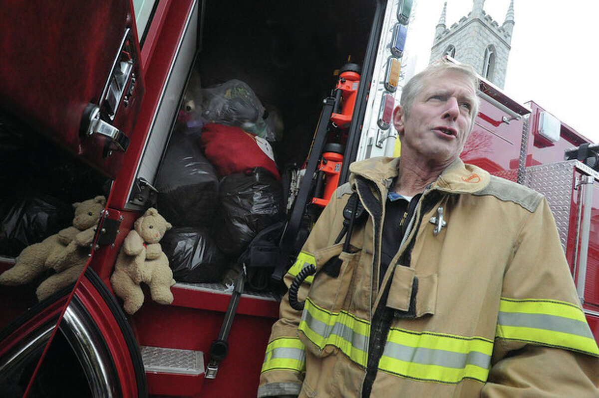Newtown firefighter Milton Adams who was a first responder at Sandy Hook Elementary on Friday takes in donated Teddy bears Sunday at Trinity Episcopal Church in Newtown. hour photo/Matthew Vinci