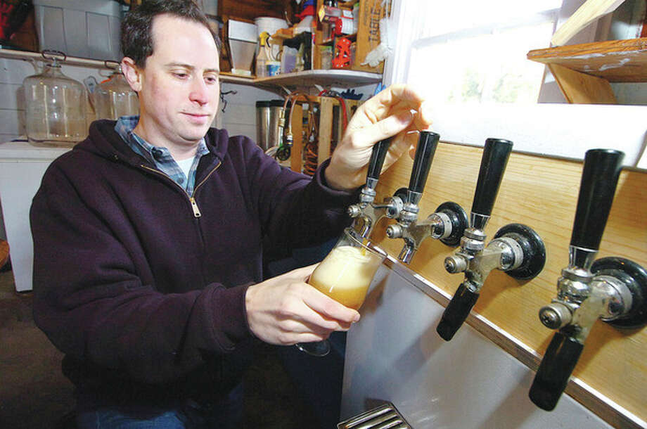 Hour photos / Alex von KleydorffJonathan Healey pours a glass of his Kiwi India Pale Ale from the tap in his Westport home brewery. A fresly poured glass of Kiwi IPA. / 2013 The Hour Newspapers