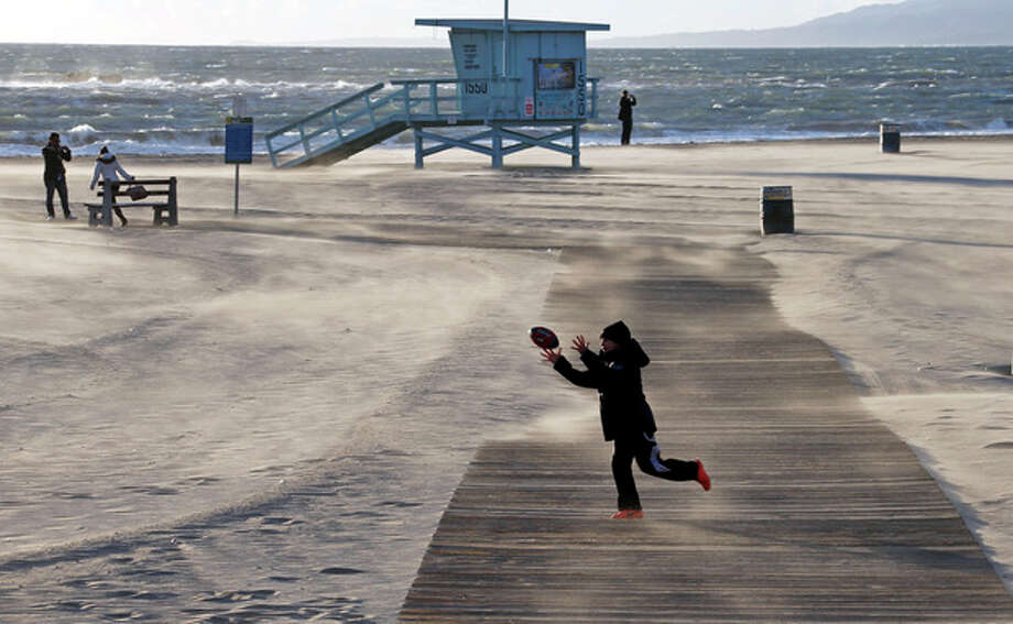 Bundled up against the elements, a boy catches a football as frigid, gusting winds blow sand in drifts across a boardwalk on a nearly-deserted beach near the pier at Santa Monica, Calif., Thursday, Jan. 10, 2013. Strawberry growers are covering their crops while San Diego zookeepers are turning on heaters for the chimpanzees as Southern California braces for a cold snap expected to drop temperatures to a six-year low. (AP Photo/Reed Saxon) / AP