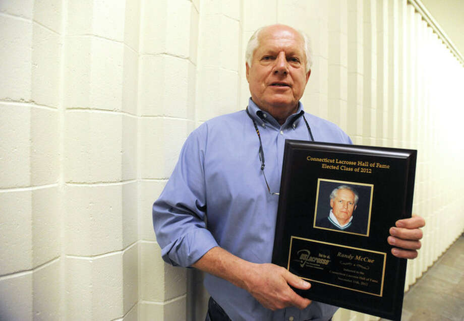 Hour photo/John NashFormer Norwalk High boys lacrosse coach Randy McCue holds the plaque he received in November upon his induction into the Connecticut Lacrosse Hall of Fame.