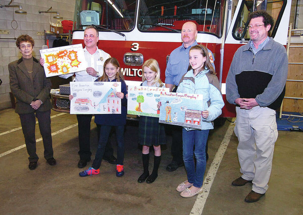 Hour Photo / Alex von Kleydorff From left, back row, Cider Mill Principal Ginny Ricco, Wilton Fire Inspector Rocco Grosso, Firefighter Dave Chaloux and Cider Mill Art teacher Mike Galullo pose with Cider Mill fourth-grader Shelby Dejana, Our Lady of Fatima fourth-grader Christina O'Sullivan and Cider Mill fifth-grader Kate Quinlan and the winning Fire Prevention poster submissions.