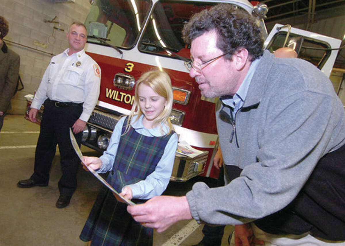 Hour photo /Alex von Kleydorff Cider Mill art teacher Mike Galullo looks at Our Lady of Fatima School's Christina O'Sullivan's Fire Prevention poster that was one of the winning entries in the Connecticut Fire Prevention Poster Contest.