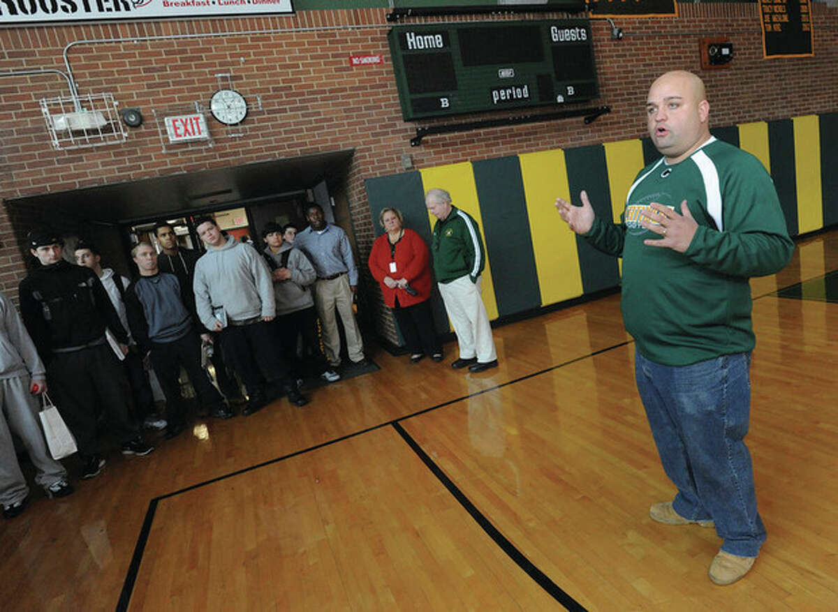 Hour photo/Matthew Vinci New Trinity Catholic football coach Don Panapada, right, speaks to his players Monday, shortly after the announcement that the Crusaders' former defensive coordinator had been named to succeed Pete Stokes, who resigned in December.
