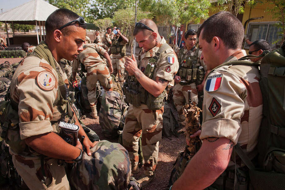 This picture released by the French Army Communications Audiovisual office (ECPAD) shows French soldiers getting ready before boarding to Bamako, the capital from Mali, at Kossei camp in N'Djamena, Chad, Friday, Jan. 11, 2013. The battle to retake Mali's north from the al-Qaida-linked groups controlling it began in earnest Saturday, after hundreds of French forces deployed to the country and began aerial bombardments to drive back the Islamic extremists from a town seized earlier this week. (AP Photo/ R.Nicolas-Nelson, Ecpad) / ECPAD
