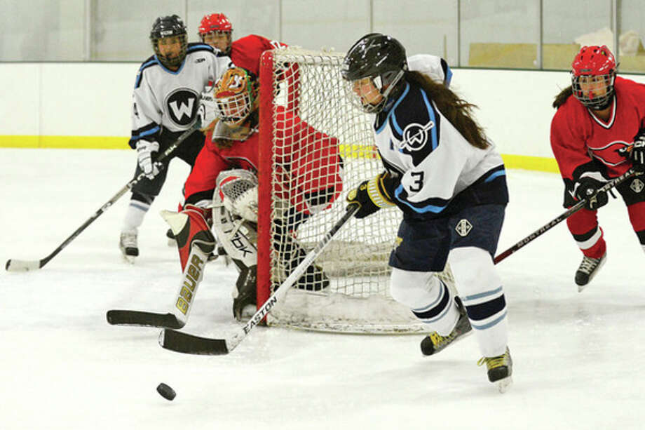 Photo by Erik Trautmann Nicole Lue (3) of the Wilton girls hockey team looks for an opening as she comes around the net during Saturday afternoonÕs game against Greenwich at the SoNo Ice House. Lue collected two goals and an assist, but Greenwich rallied for a 4-3 victory. / (C)2012, The Hour Newspapers, all rights reserved