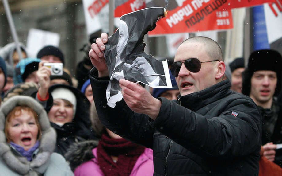 AP photo / Misha JaparidzeOpposition leader Sergei Udaltsov, foreground, burns a portrait of Russian President Vladimir Putin during a protest rally in Moscow, Russia, Sunday. Thousands of people are gathering in central Moscow for a protest against Russia's new law banning Americans from adopting Russian children. They carry posters of President Vladimir Putin and members of Russia's parliament who overwhelmingly voted for the law last month. / AP