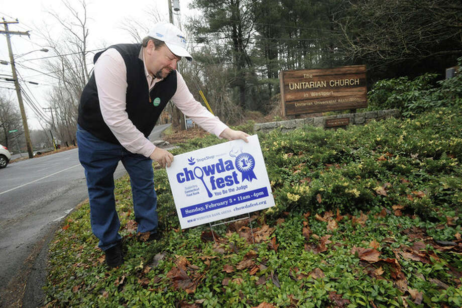 Hour photo/Matthew VinciJim Keenan, organizer of the Chowder Festival, puts up signs in Westport Sunday to promote the Feb. 3 event at the Webster Bank Arena at Harbor Yard in Bridgeport.