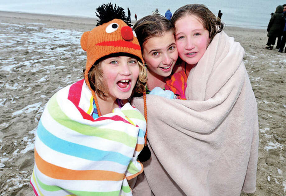 Allison Pavloff, 10, Gabrielle, Rodia, 10 and Michelle Pavloff, 12, warm up after particip[ating in the Team Mossman Triathlon Club's 10th annual 'polar plunge' at Compo Beach Tuesday to benefit Save the Children.Hour photo / Erik Trautmann / (C)2012, The Hour Newspapers, all rights reserved