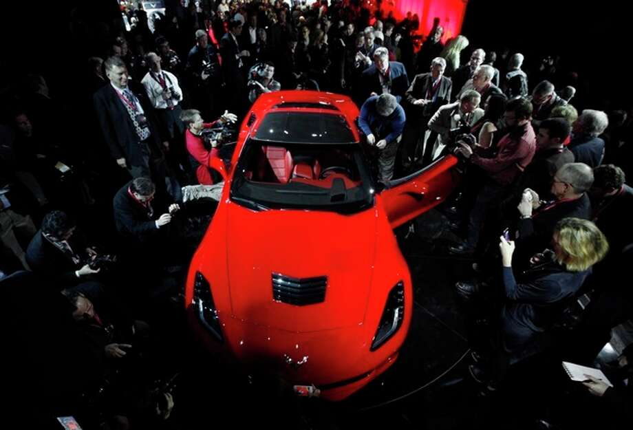 Journalists surround General Motors new 2014 Chevrolet Corvette Stingray, Sunday, Jan. 13, 2013, the night before press days at the North American International Auto Show in Detroit. When 1,000 GM engineers and designers started work on the next-generation Corvette, they began with the usual priority list for a muscle car. Killer looks. Big engine. Fast. But topping the list was something that belies the roar of the Chevrolet's giant V-8: Gas mileage. (AP Photo/Paul Sancya) / AP