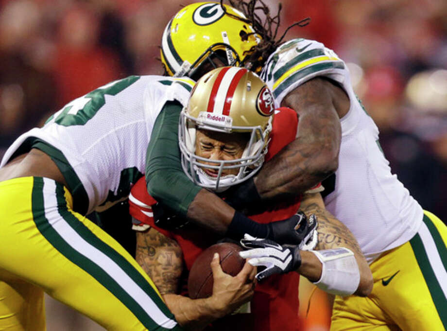 San Francisco 49ers quarterback Colin Kaepernick (7) is tackled by Green Bay Packers free safety M.D. Jennings (43) and outside linebacker Erik Walden (93) during the second quarter of an NFC divisional playoff NFL football game in San Francisco, Saturday, Jan. 12, 2013. (AP Photo/Marcio Jose Sanchez) / AP