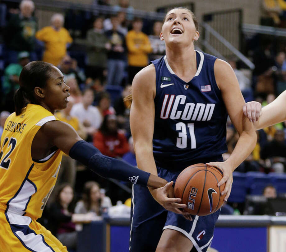 Connecticut's Stefanie Dolson (31) is fouled by Marquette's Sarina Simmons, left, during the first half of an NCAA college basketball game Saturday, Jan. 12, 2013, in Milwaukee. (AP Photo/Jeffrey Phelps) / FR59249 AP