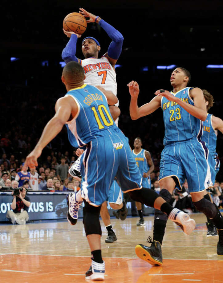 New York Knicks forward Carmelo Anthony (7) shoots over the defense of New Orleans Hornets guard Eric Gordon (10) as Hornets forward Anthony Davis (23) watches in the first half of their NBA basketball game at Madison Square Garden in New York, Sunday, Jan. 13, 2013. (AP Photo/Kathy Willens) / AP