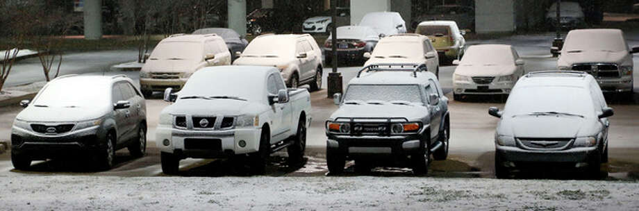 Cars in this car dealer's lot in Flowood, Miss., show the accumulation of snow early Thursday morning Jan. 17, 2013, in Flowood, Miss. The National Weather Service says central Mississippi could get from 2 to 4 inches of snow from midnight through midmorning Thursday. (AP Photo/Rogelio V. Solis) / AP