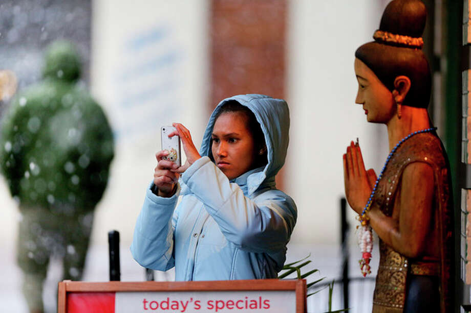 While standing in front of Thai Continental Cuisine restaurant, Kratai Fisher takes a picture of heavy snow falling in downtown Roanoke, Virginia on Thursday afternoon Jan. 17, 2013. Virginia is bracing for the first significant snowstorm of the winter season. (AP Photo/The Roanoke Times, Kyle Green) LOCAL TV OUT; SALEM TIMES REGISTER OUT; FINCASTLE HERALD OUT; CHRISTIANBURG NEWS MESSENGER OUT; RADFORD NEWS JOURNAL OUT; ROANOKE STAR SENTINEL OUT MBI / The Roanoke Times