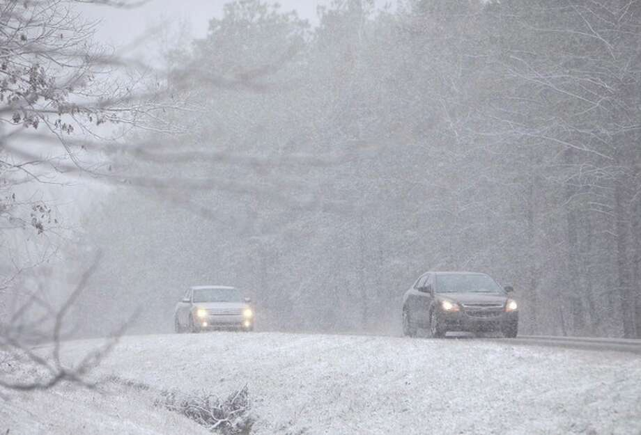 Vehicles move along Hwy 86 in Carrollton, Ala. Thursday, Jan. 17, 2013. A wet blanket of snow covered much of West Alabama Thursday morning. (AP Photo/The Tuscaloosa News, Dusty Compton) / Tuscaloosa News
