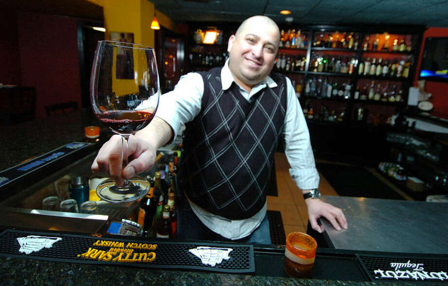 Hour Photo Alex von Kleydorff; Tinto, Bar Tapas owner Carlos Hernandez raises a glass of Spanish wine in the bar of Tinto in Norwalk