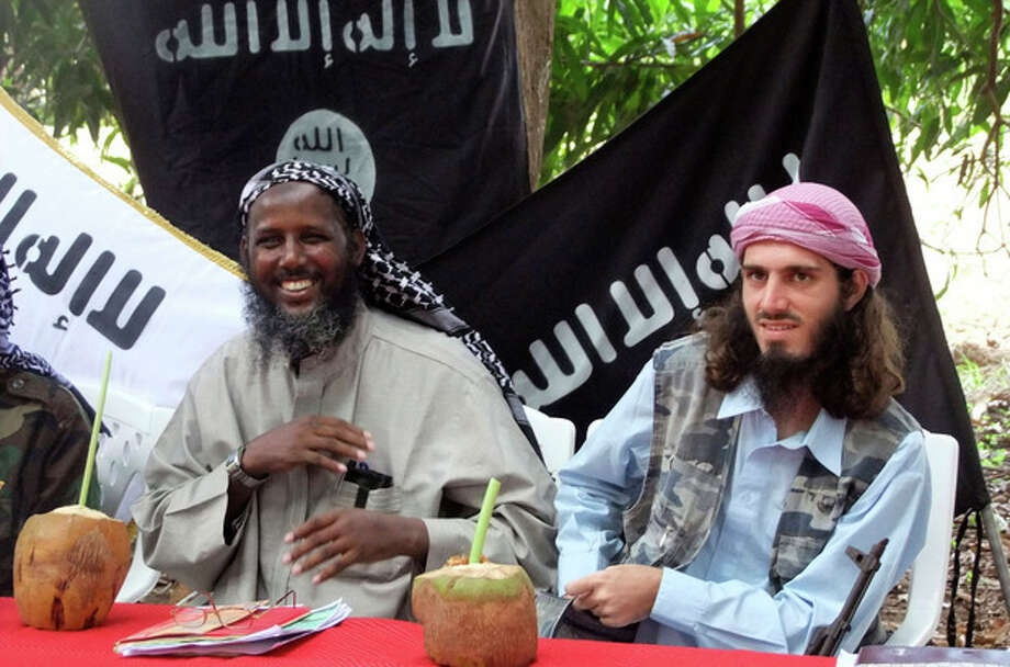 """FILE - In this Wednesday, May 11, 2011 file photo, American-born Omar Hammami, also known as Abu Mansur al-Amriki, right, and deputy leader of al-Shabab Sheik Mukhtar Abu Mansur Robow, left, sit under a banner which reads """"Allah is Great"""" during a news conference by the militant group at a farm in southern Mogadishu's Afgoye district in Somalia. Hammami - whom the FBI named as one of its most wanted terrorists in November - has engaged in a public fight with al-Shabab over nearly the last year and may soon find himself the one pursued by insurgents. (AP Photo/Farah Abdi Warsameh, File) / AP"""