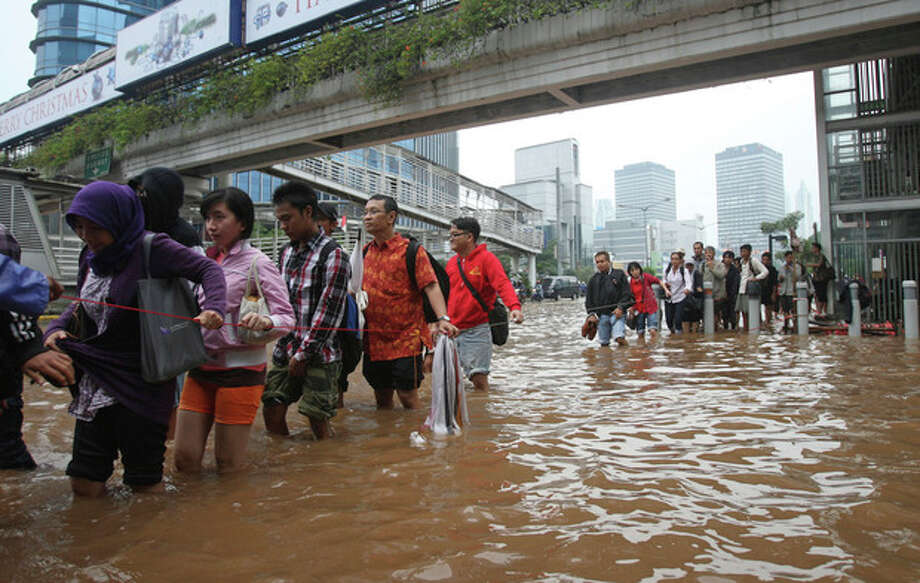 People cross a flooded street while holding a cord for safety in Jakarta, Indonesia Friday, Jan. 18, 2013. Indonesia's army deployed rubber boats in the capital's business district on Thursday to rescue people trapped in floods that inundated much of the city of 14 million people. (AP Photo/Achmad Ibrahim) / AP